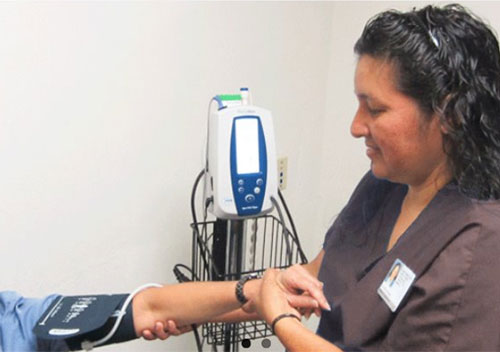 Image shows a health care person wearing brown scrubs administering a blood pressure check. Only the patient's arm is showing in this photo
